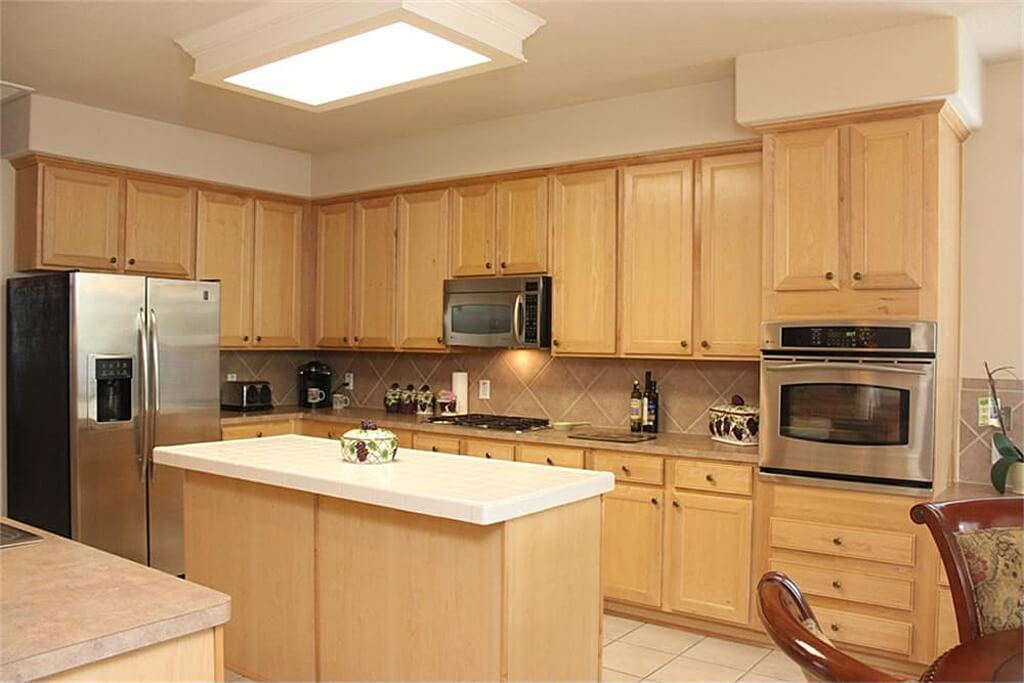 U-shaped kitchen with walnut cabinetry and counters along with a small center island equipped with smooth white countertop.