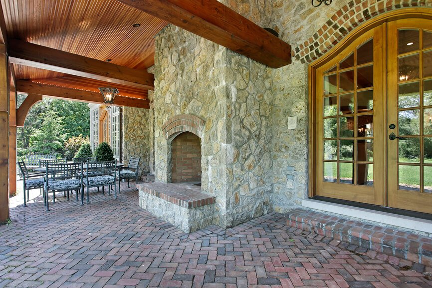 This fireplace is built against the side of the home's stone facade, blending perfectly. It extends through the top of the wooden roof of the patio and has a raised hearth that matches the brick of the patio.