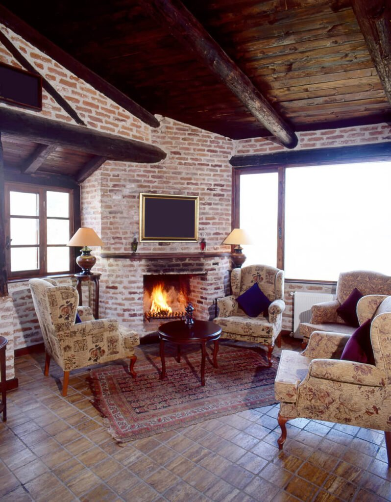 Three cozy looking wingback chairs around a round table and a fireplace. These chairs are welcoming and cozy, and a great deat to have next to a roaring fire.