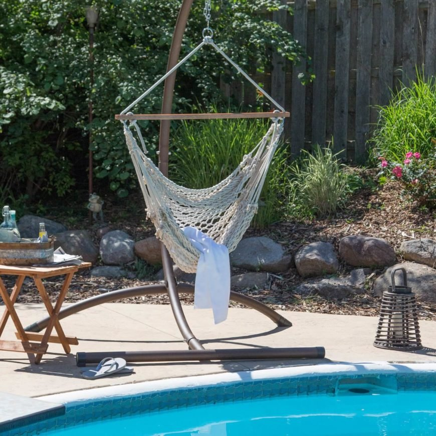 A hammock chair complete with a sturdy stand by the side of the pool. The open weave is perfect for feeling the breeze and drying off after a dip in the pool.