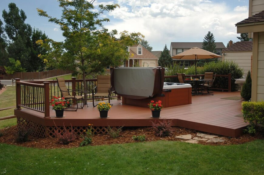 A beautiful wooden deck with a latticed screen around the lower part to keep out rodents and other pests. The deck is in a rich cedar stain and has plenty of space for several seating areas in addition to a hot tub.