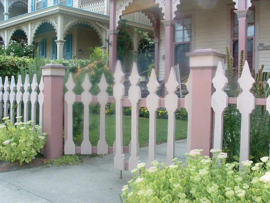 Varied color and size contrasts the posts from the fence itself in this picket style fence.