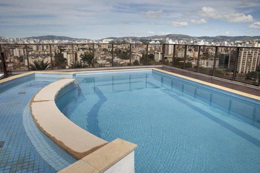A simple mesh fence surrounds this rooftop pool, allowing a view of the cityscape.