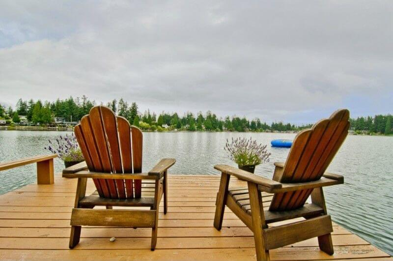 A set of adirondack chairs sit at the end of a dock with two planters filled with lavender. They look out over a pristine, calm lake.