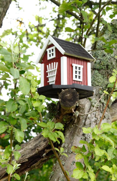 A crisply painted red and white barn-shaped birdhouse perched on a sawn-off branch in a mature tree.
