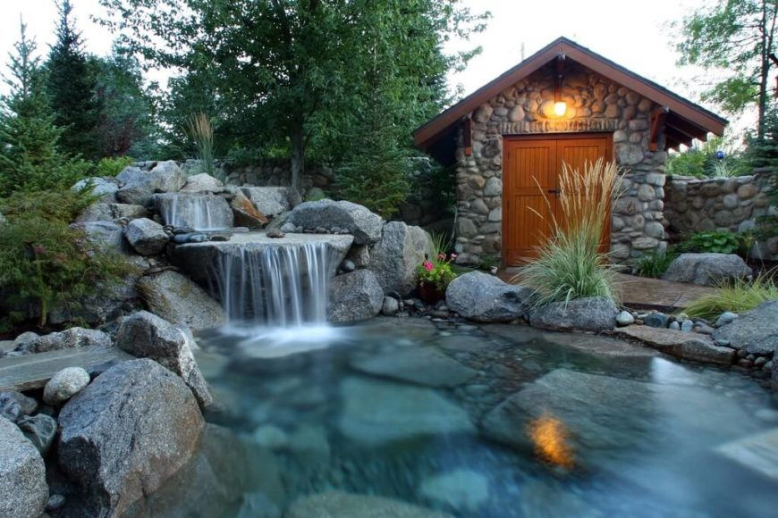 The river stone siding on this backyard shed blends it into the overall landscaping of the yard.