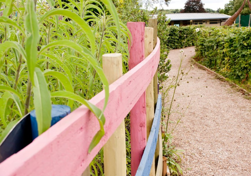 Posts of variable length and color can spice up an otherwise traditional fence design.