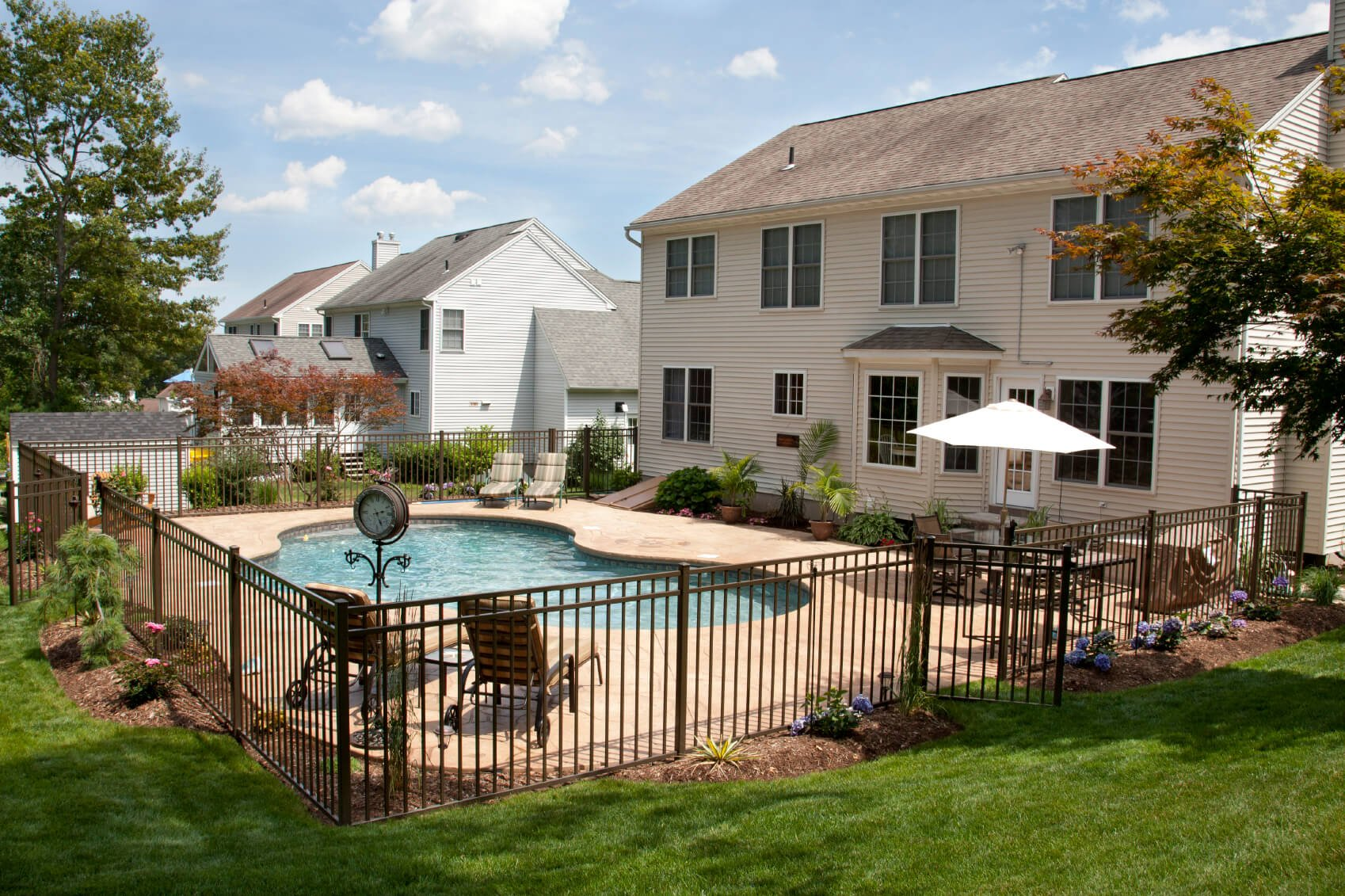 This is a simple black metal post fence. this is a very simple and utilitarian way to fence off your pool. It is a classic, simple and easy to manage option. It also creates minimal obstruction of the view.