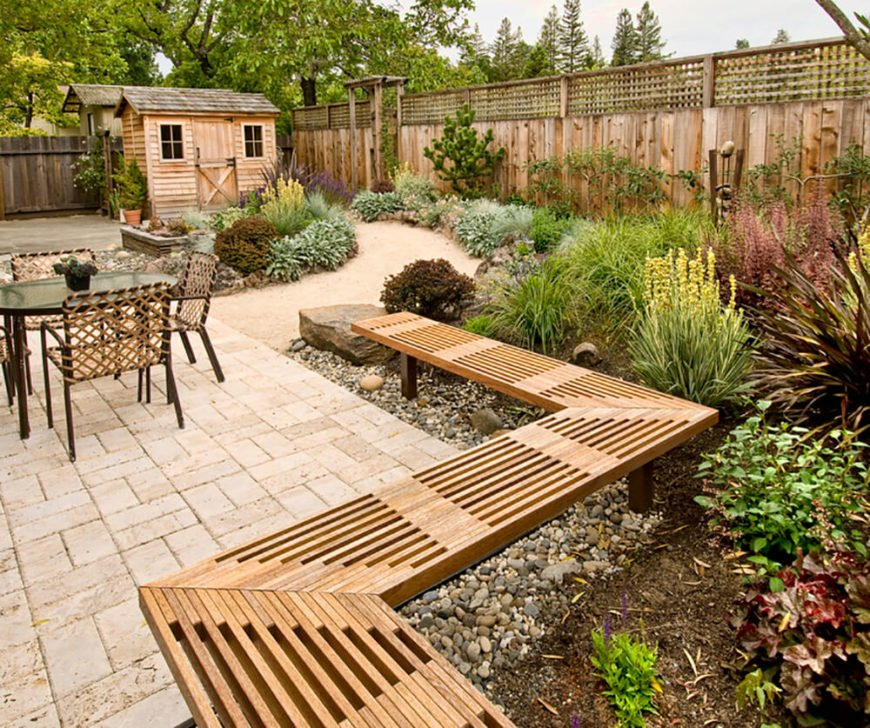 Here's another example of how lattice fences are used as decoration on top of privacy fences. Another notable element of this backyard is the zig-zagging bench along the planting beds.