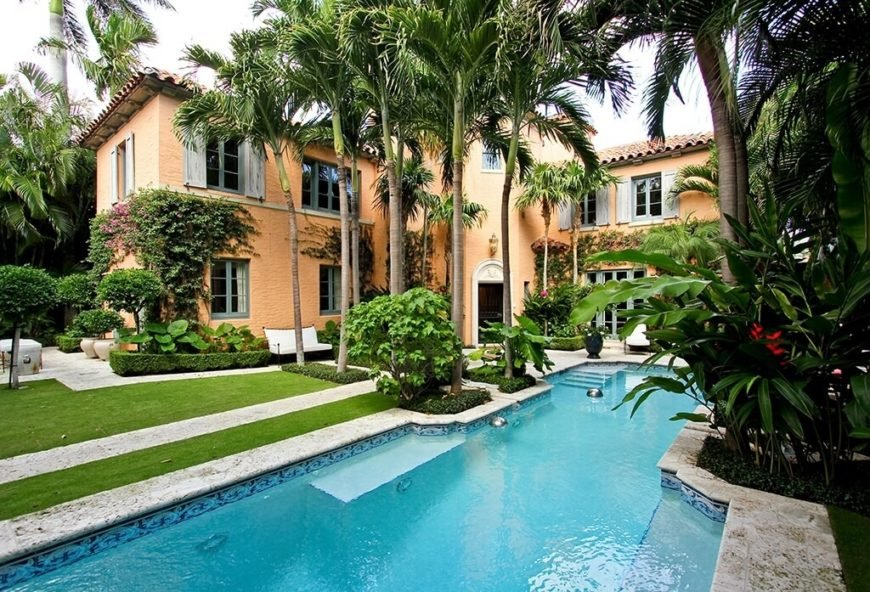 Tall palms frame the walkway that leads to the enormous swimming pool in the backyard of this enormous, classy home.
