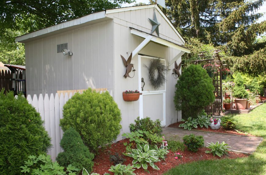 This garden shed is actually fenced off by a decorative fence in addition to a privacy fence that surrounds the yard. Nearby is an arbor and plenty of potted trees.