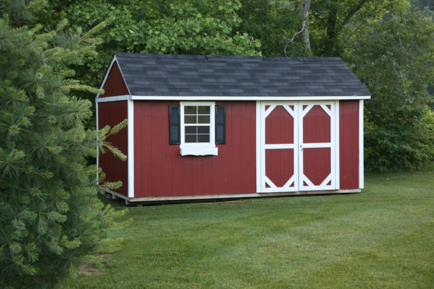 This pretty red shed is built to resemble an old country barn, and has cute shutters and a dark slate roof.