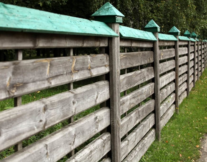 An alternate color topper sits on this raw wood fence