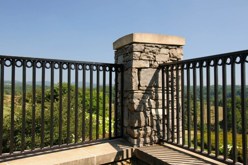 A wrought iron fence without top barbs, with a stone pillar post.