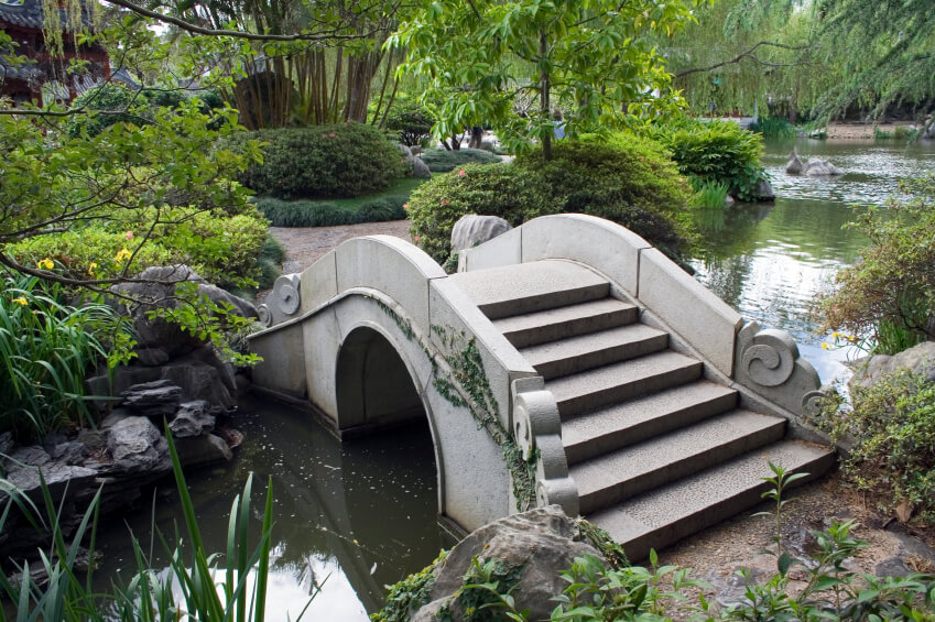 An ornate concrete bridge across a wide but shallow and slow-moving creek. This bridge connects two sections of an expansive, lush garden.
