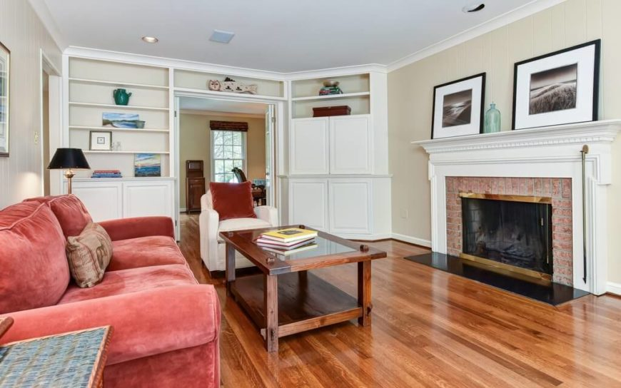 This living room has a number of long horizontal simple built in shelves that even go over the doorway. These are a good way to make use of otherwise unused space above doors.