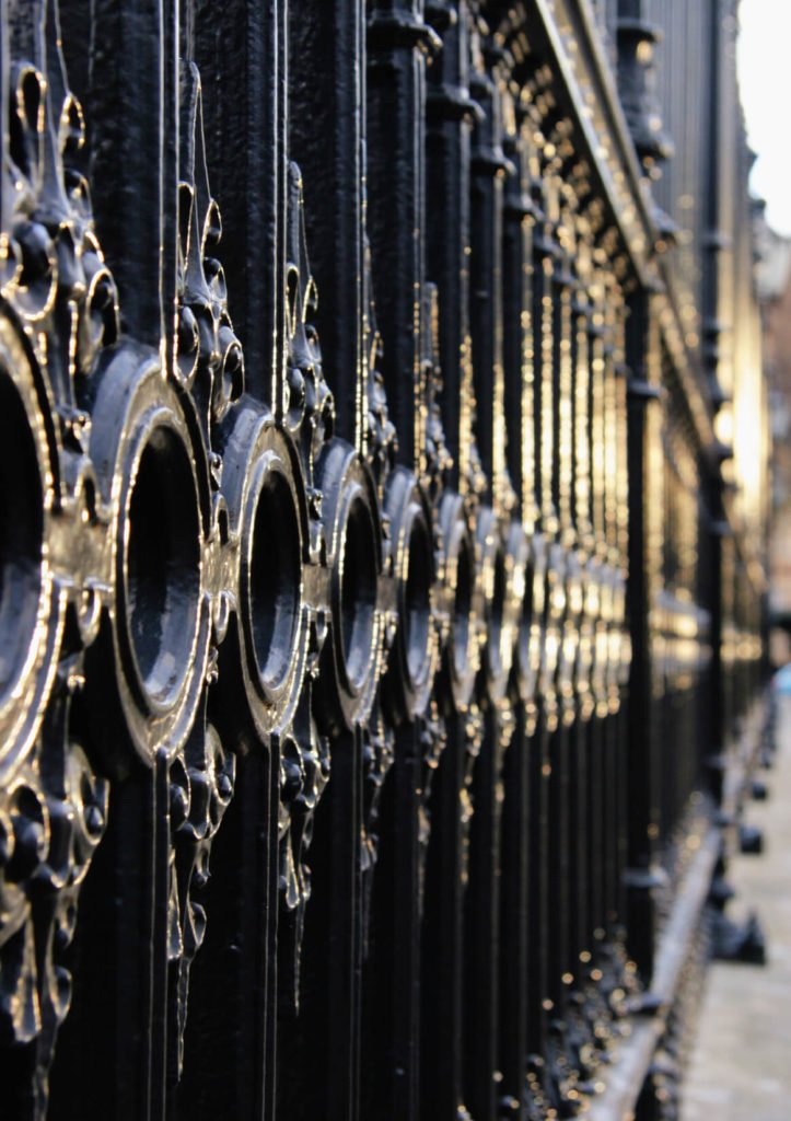 A close up of some of the details in a beautiful wrought iron fence.