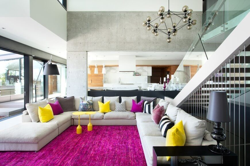 A very colorful carpet and pillows give this simple room a very fun appeal.