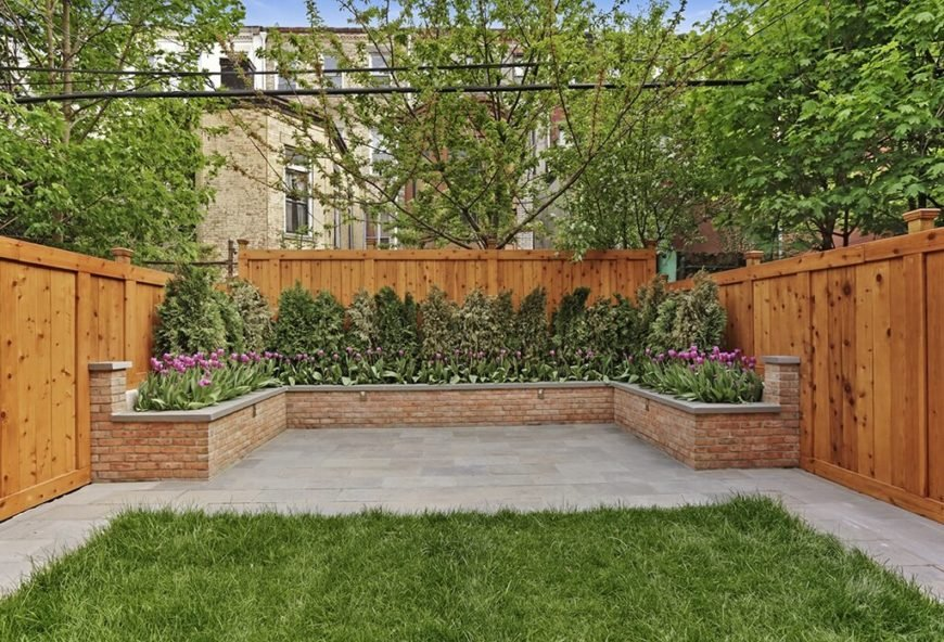 This finished fence wraps around a brick flowerbed.