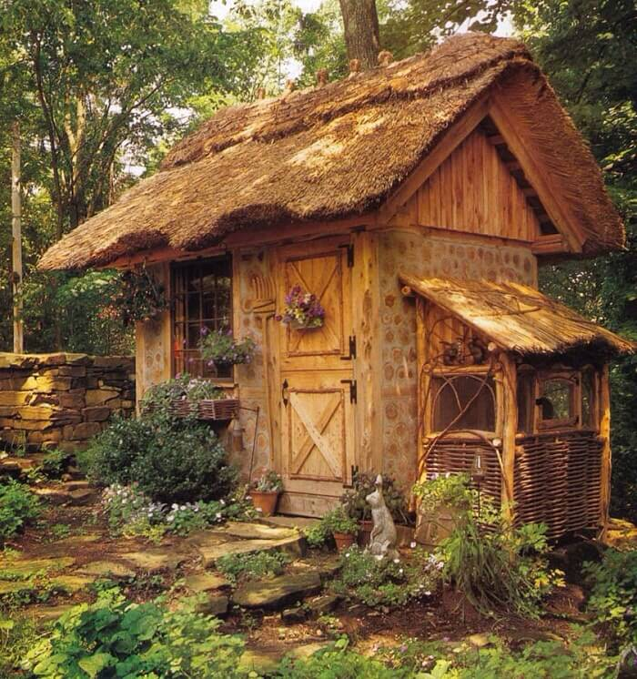 Thatch roofing and dutch doors are perfect accents for this cozy cottage-style shed.