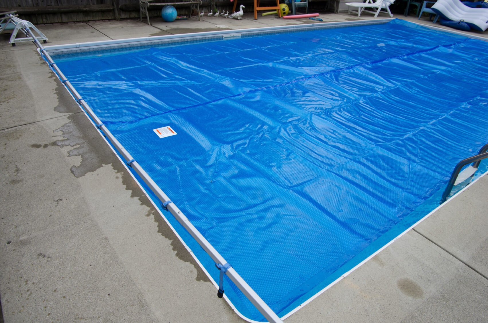 This is a long rectangular pool with a standard solar cover on it. The tarp is connected to a bar on the end of the pool for easy retraction. This reduces the hassle of constantly replacing and removing the cover if you are using it to help heat the water.
