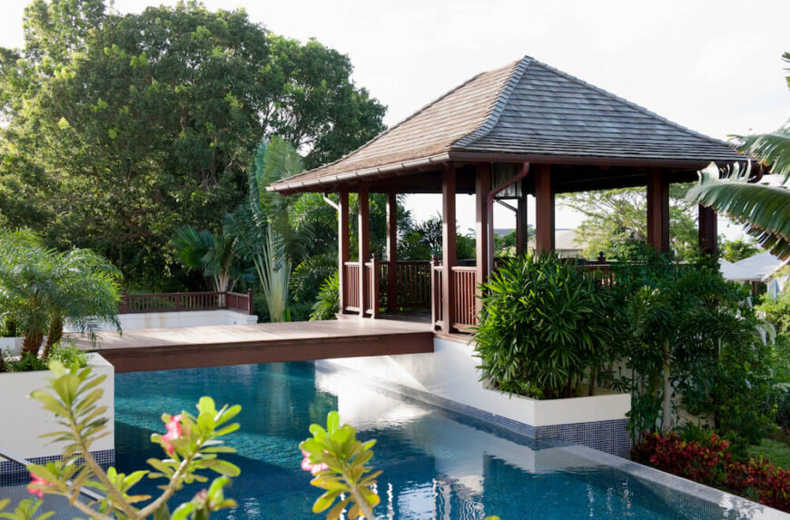 A poolside gazebo attached to the main concrete patio by means of a simple wooden foot bridge with no railings. The property is surrounded by tropical flora and overlooks the sea.