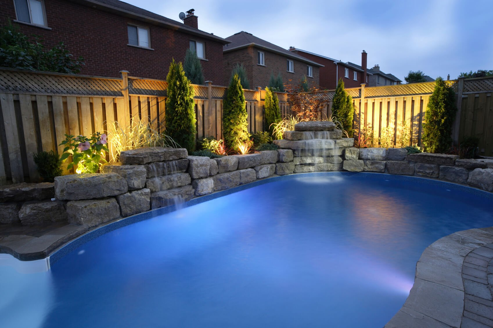 A tall wooden fence is classic. With a tall fence, you can have a bit of privacy for you and your family while taking a dip in your pool.