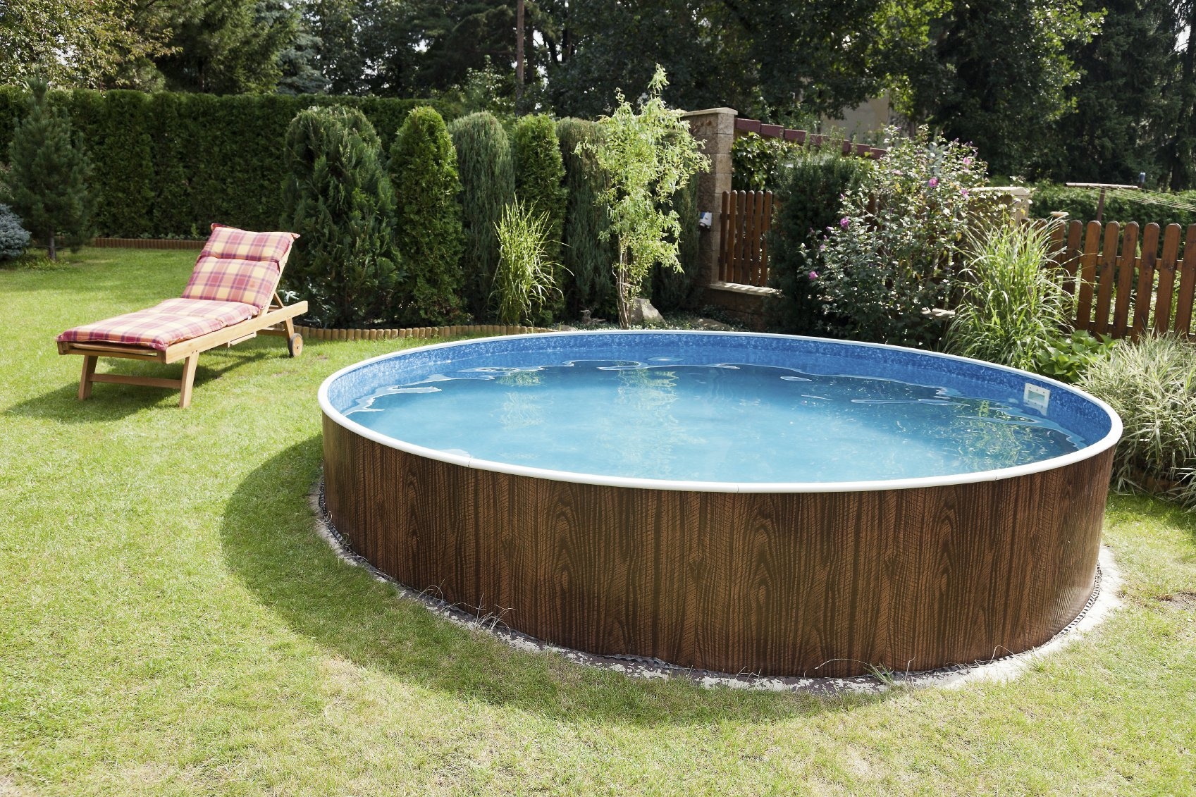 When getting an above-ground pool, you don't have to get fancy or build leveled decks. Sometimes a simple approach works well. This round above-ground pool stands alone, with a vintage wood panel look.