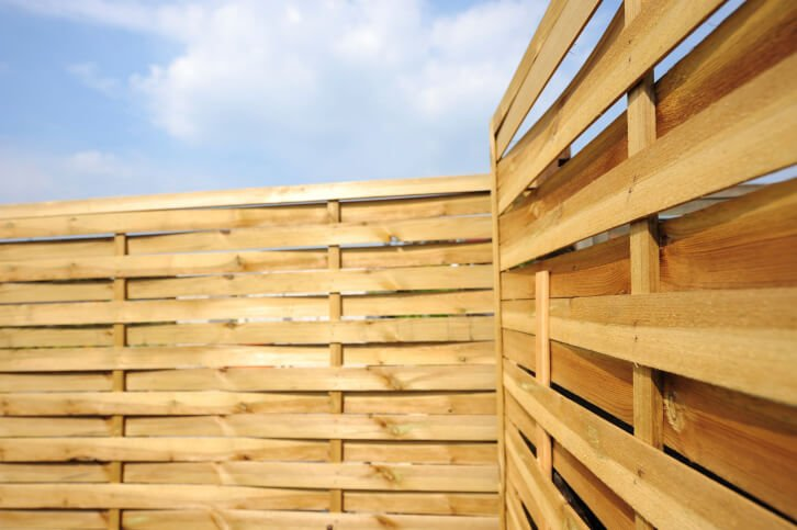 This privacy fence is in a much lighter stain, but the slats are staggered to allow the breeze through. This is a great design for areas that see severe weather.