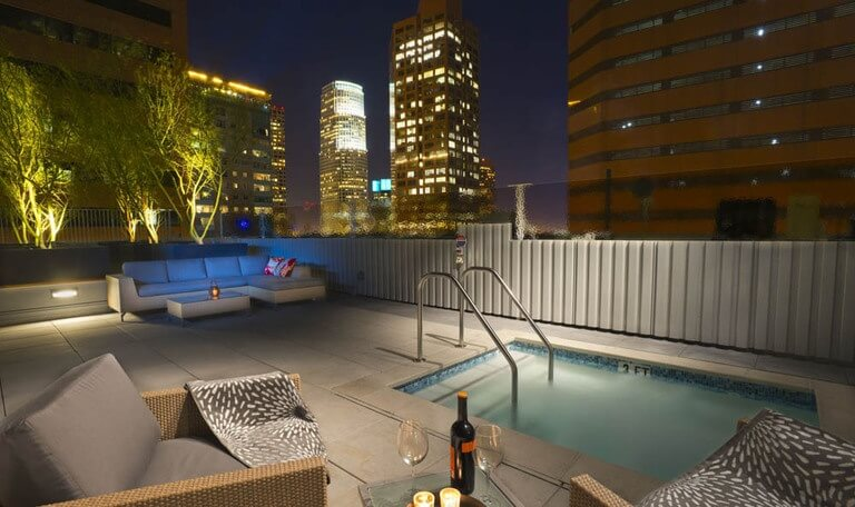 A sleek modern vinyl fence in beige that surrounds this lovely patio and pool. The vinyl fence is topped by glass panels that slightly obscure the city lights pouring in.