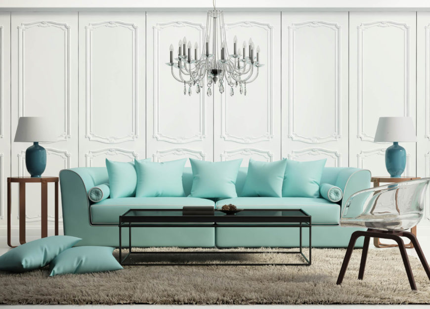 A sofa and lamps stand out in this mostly white room. A sofa is a great place to add color and a great deal depth and appeal.