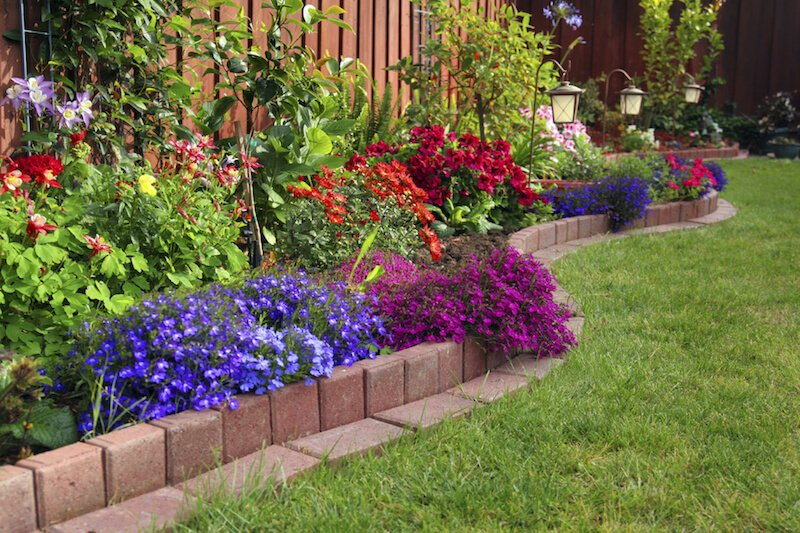 If you prefer a smooth edge, use pavers to easily define your flower beds. Then feel free to allow your plants mingle in an explosion of color.