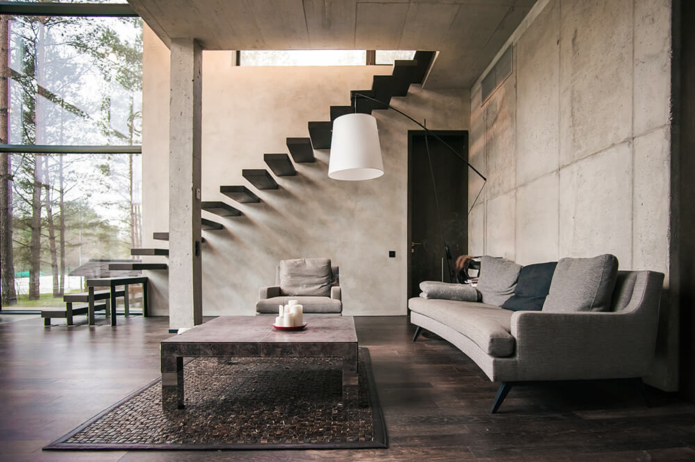 Inside the home we can see the same minimalist elements, from the concrete walls to the floating stairs leading up to the second floor. Gentle curvatures in the sofa break up the sharp, geometric lines of the coffee table and walls.