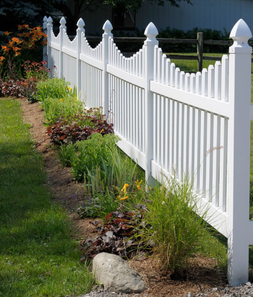 A lovely vinyl picket fence in white that meets a split rail fence. When fences are used for mostly decorative reasons, this can be a great way to save money. Choose a less expensive fence on the sides where your fence won't be visible from the road.