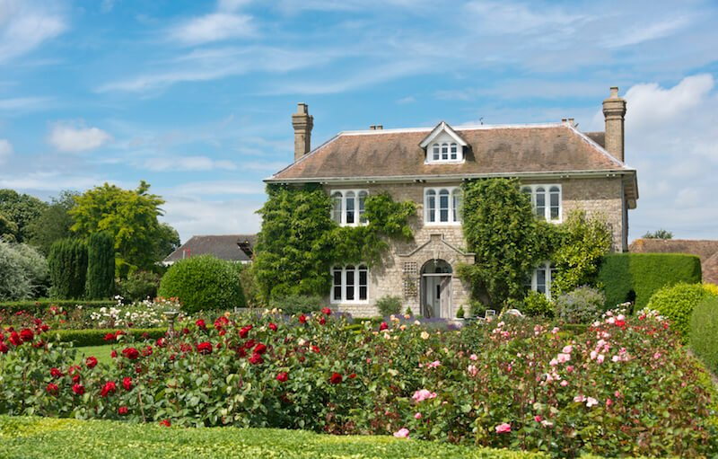 This country estate is filled with slightly overgrown rose bushes, creating a magical and beautiful display.