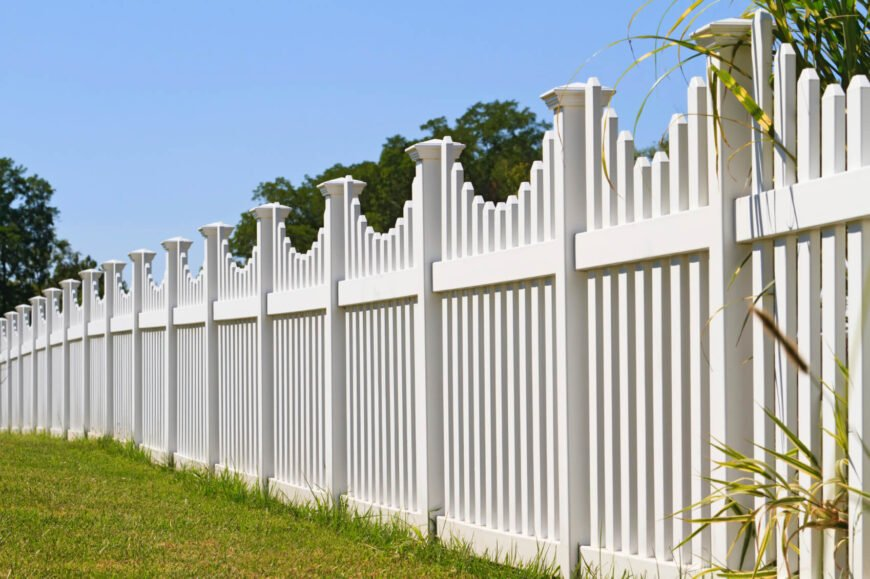 Another lovely white vinyl picket fence with square post caps and a small curvature to each panel of the fence. This fence runs the length of a rather large yard. Only a few bits of plant life from the other side poke through.