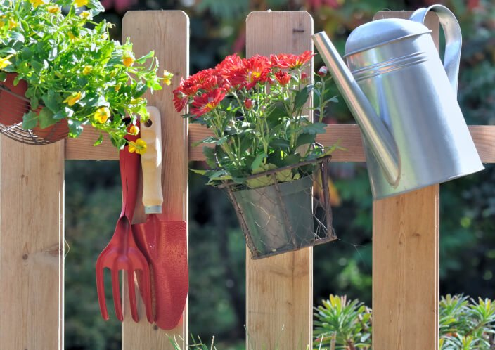 Lights and plants are not the only thing that you can hang from a fence post. Bring some utility to your fence by hanging gardening supplies like this fence has.