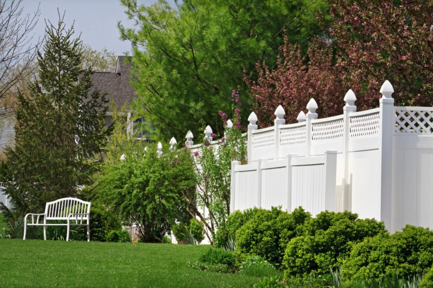 A tall vinyl wood-look privacy fence topped with lattice for additional style. Tall bushes and flowering trees cover parts of the bright white fence.