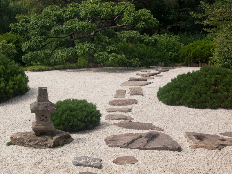 This zen garden focuses namely on sand and stone, but has a few patches of sturdy, thick shrubs.