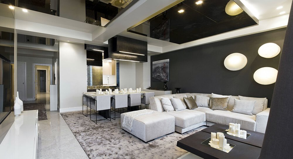 A great room with a luxurious setup. The tray ceiling is just so stunning along with the black walls.