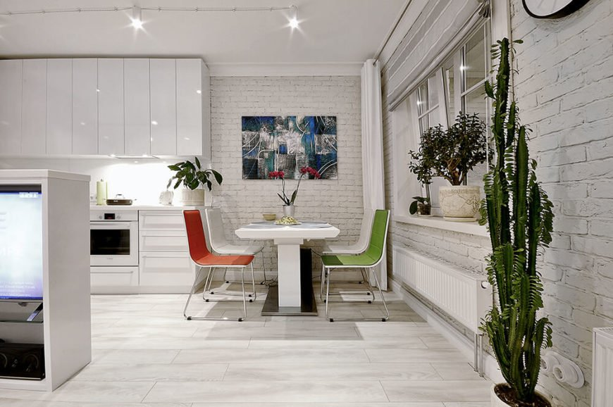 The small dining room area is located immediately to the right of the kitchen, across from the living room sectional. House plants and colorful chairs add color back into the mostly white area.