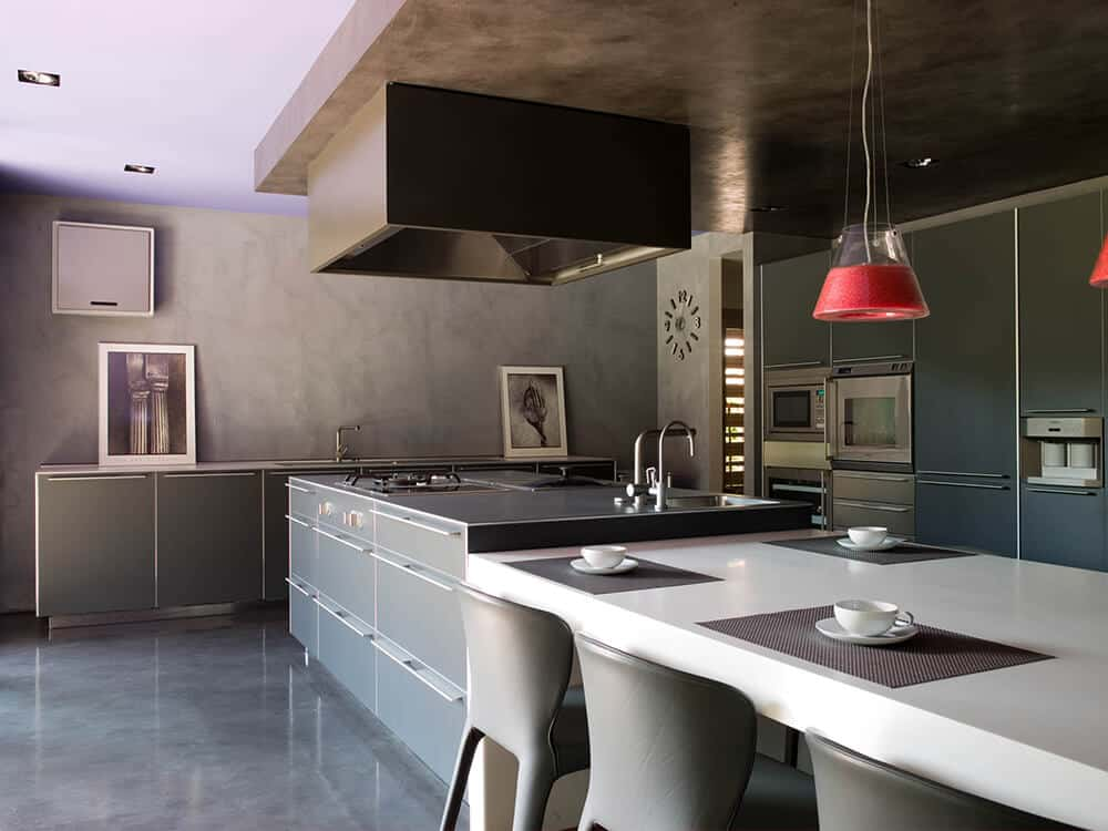 Large kitchen featuring a large gray center island and a white dining nook lighted by attractive pendant lights.
