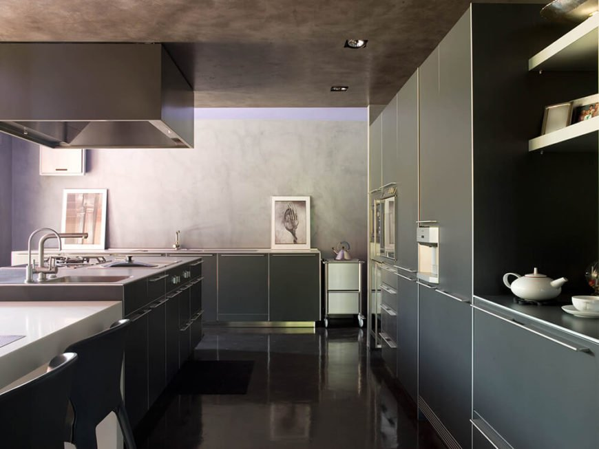 The glossy black flooring contrasts nicely with the minimalist, matte cabinetry with steel hardware. The clean, clinical look of the kitchen makes it stand out even within this home.