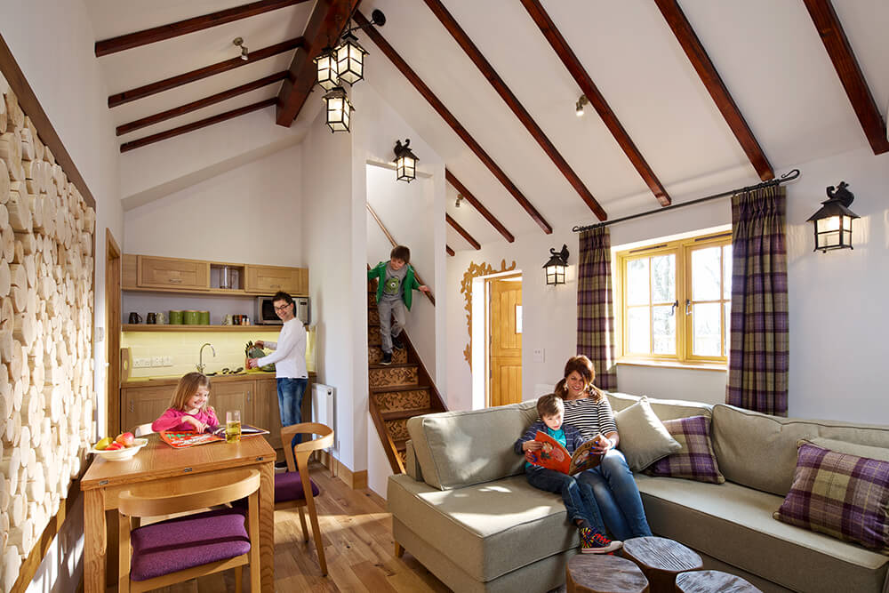 This interior shot shows the spacious interior living space of the tree house, featuring a kitchenette, dining area, and a sectional sofa. Exposed beams and intricate carvings throughout enhance the atmosphere.