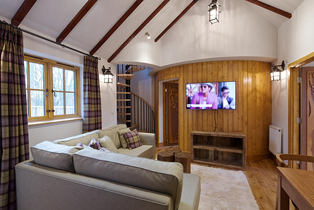 Craftsman living room offers wood plank flooring that complements with the accent wall mounted with a flat panel TV along with cathedral ceiling lined with dark wood beams.