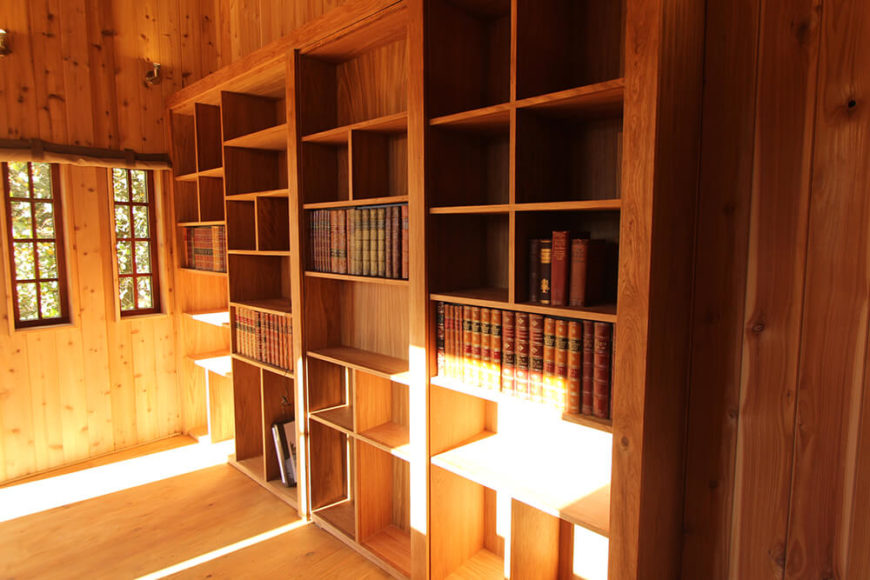 To the right is a large bookcase built into the wall. This extravagant creation offers plentiful space for display, as well as a secret.