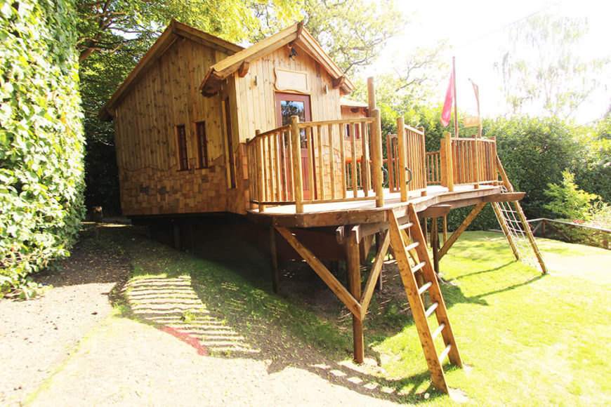 """Returning to the exterior, we see how the treehouse is built into a hill, offering plentiful """"secret"""" space beneath the deck for adventuring and egress."""