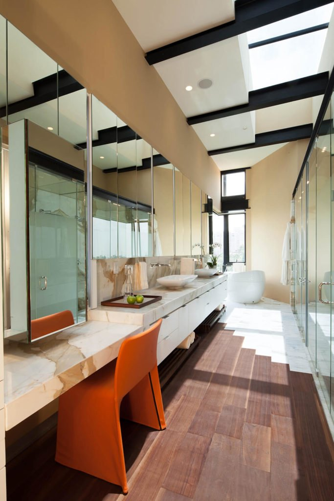 The primary bathroom is awash in rich marble and glass, with a lengthy vanity facing a row of walk-in showers and bath areas. The hardwood flooring gives way to white marble as it approaches the pedestal tub.