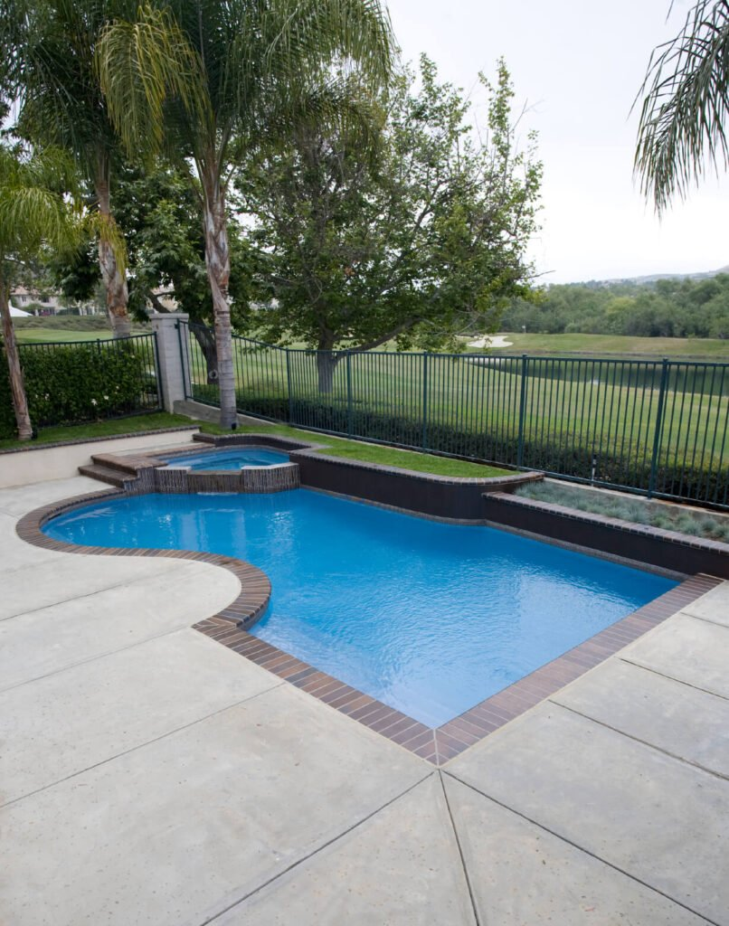 An interestingly designed small pool at the back end of a patio area. The various angles and levels make a dynamic and beautiful pool area.