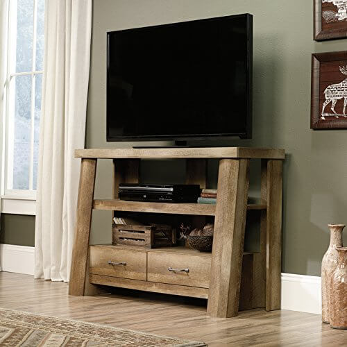 The unvarnished tone of the wood used in this gorgeously simple TV stand gives it an almost rustic look, but the sturdy framing, thick wood, and sharply creased drawers nail the Craftsman look. A stand like this would work perfectly in a similarly trimmed room, or stand out as an accent in a more modern styled space.